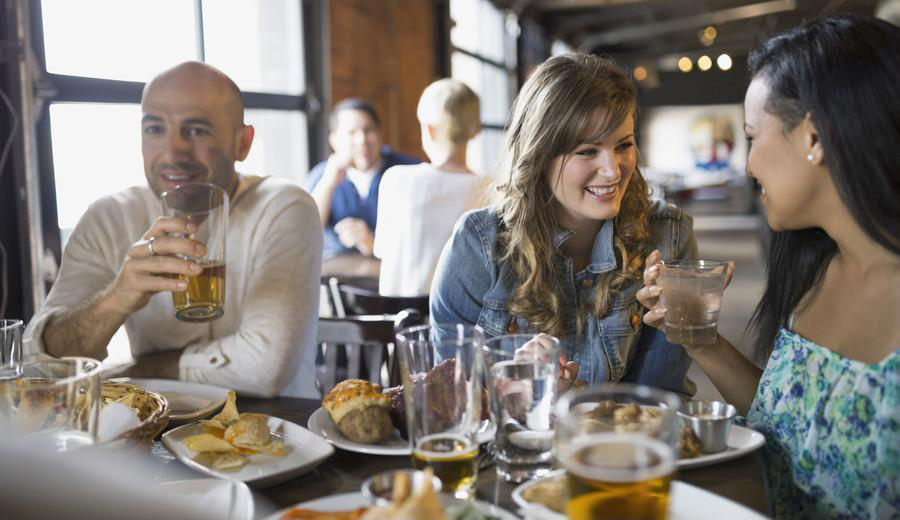stock-photo-friends-talking-and-eating-in-pub-83224261